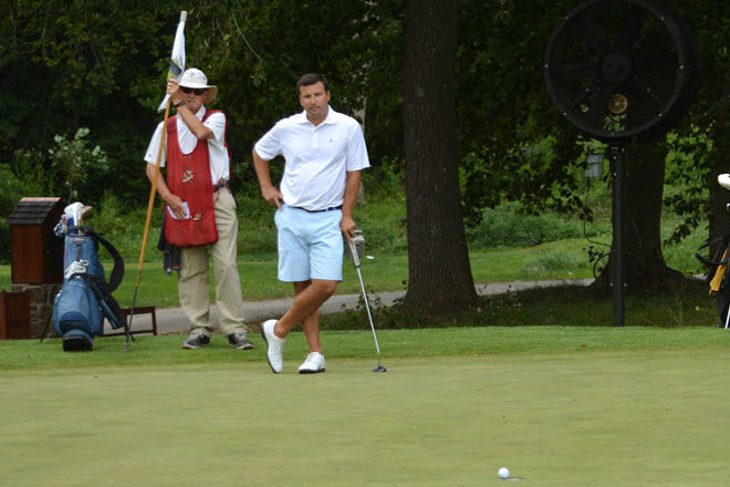 Tom Spano discusses his putt with his caddie.